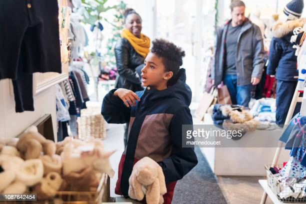 Mixed-race family shopping in children store in winter.