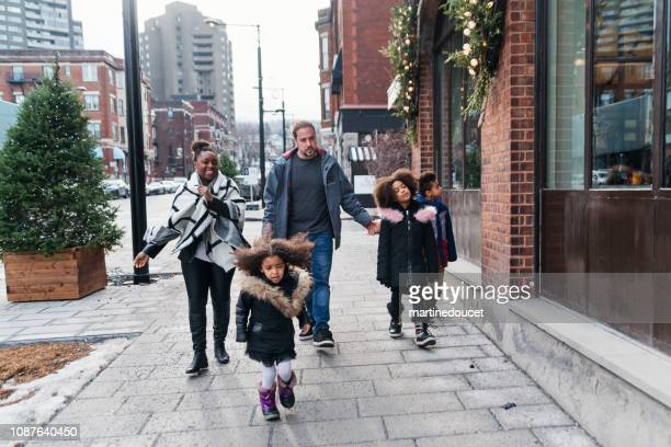 """mixed-race family shopping on city street in winter. - """"martine doucet"""" or martinedoucet stock pictures, royalty-free photos & images"""
