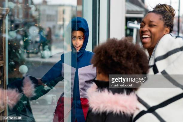 Mixed-race family shopping on city street in winter.