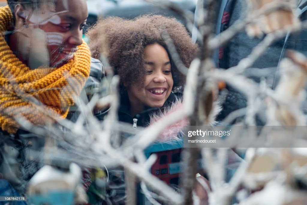 Mixed-race family shopping on city street in winter. : Stock Photo