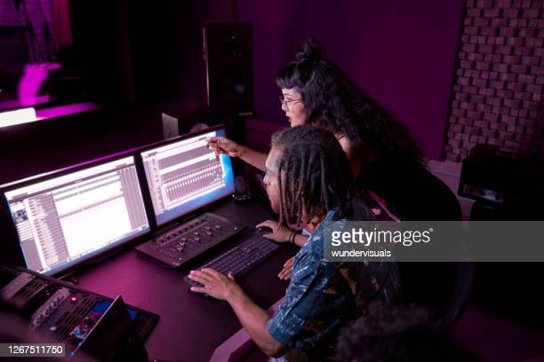 mixed-race female artist working with african-american music producer on her song in music studio - songwriter stock pictures, royalty-free photos & images