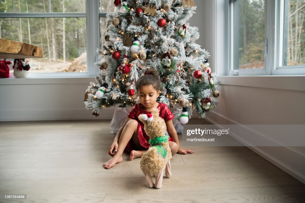 Mixed-race little girl day dreaming in front of the Christmas tree. : Stock Photo