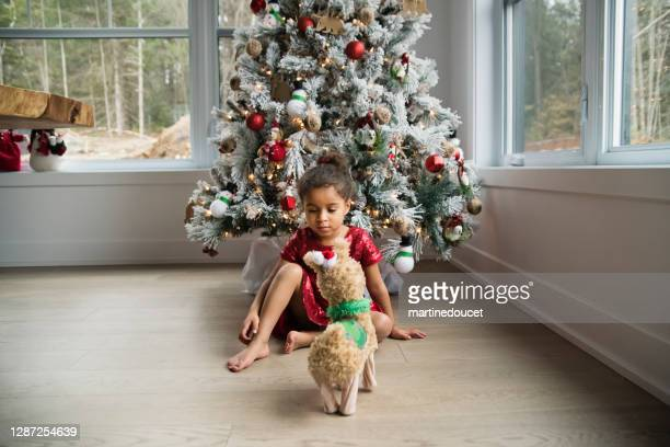 """mixed-race little girl day dreaming in front of the christmas tree. - """"martine doucet"""" or martinedoucet stock pictures, royalty-free photos & images"""