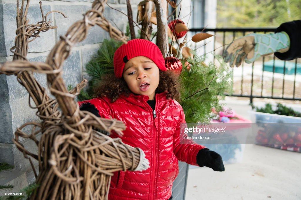 Mixed-race little girl painting diy seasonal outdoors decorations. : Stock Photo