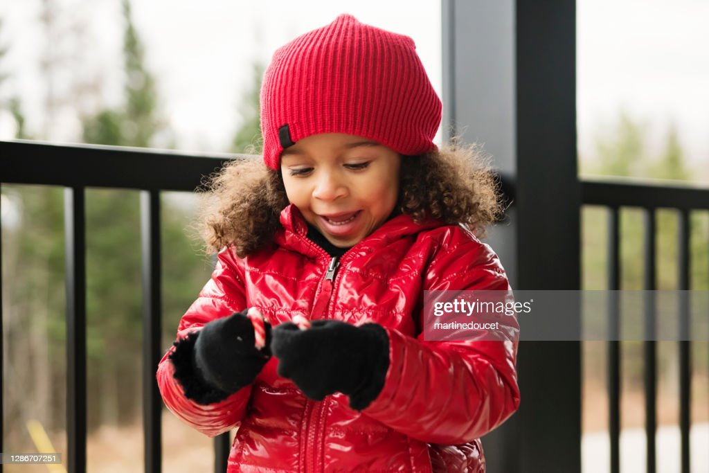 Mixed-race little girl playing with christmas candy cane. : Stock Photo