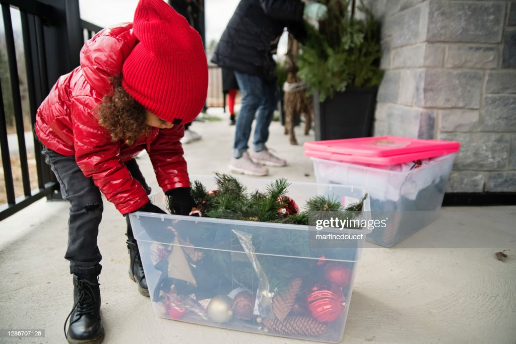 Mixed-race little girl playing with seasonal outdoors decorations. : Stock Photo