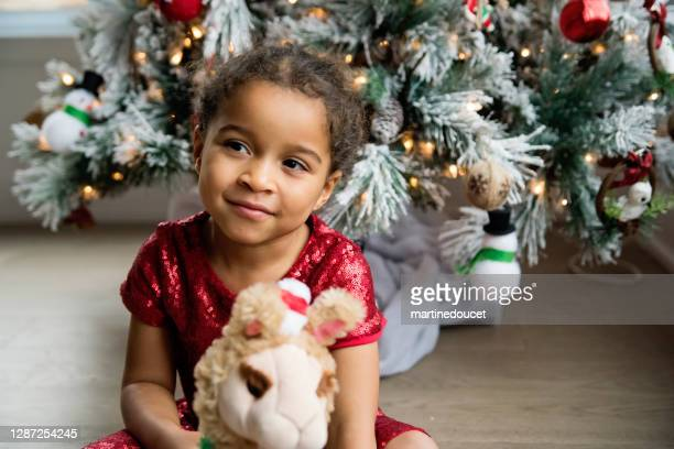 """mixed-race little girl portrait in front of the christmas tree. - """"martine doucet"""" or martinedoucet stock pictures, royalty-free photos & images"""