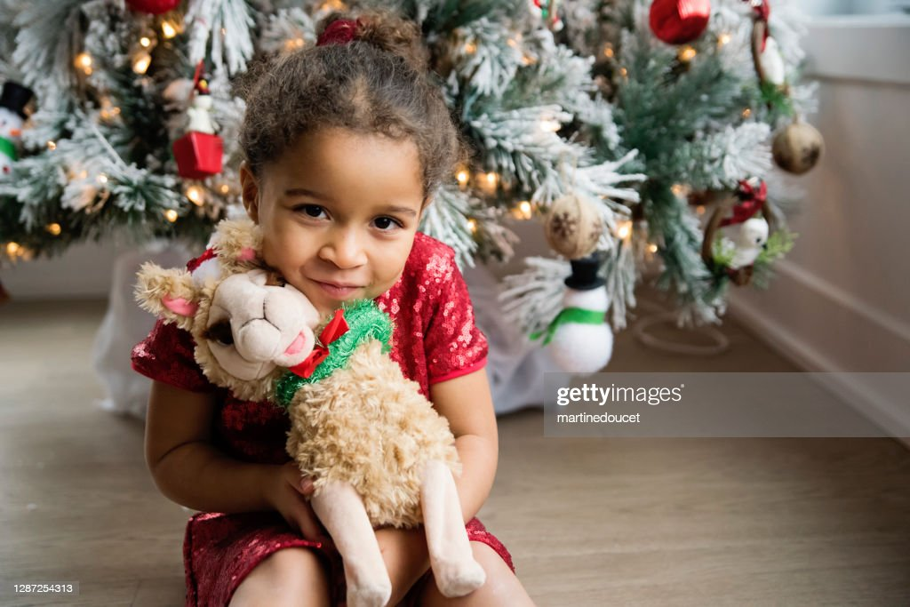 Mixed-race little girl portrait in front of the Christmas tree. : Stock Photo