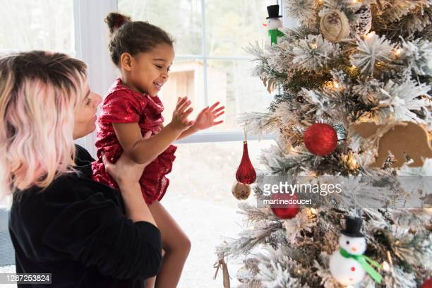 """mixed-race mother and daughter decorating the christmas tree. - """"martine doucet"""" or martinedoucet stock pictures, royalty-free photos & images"""