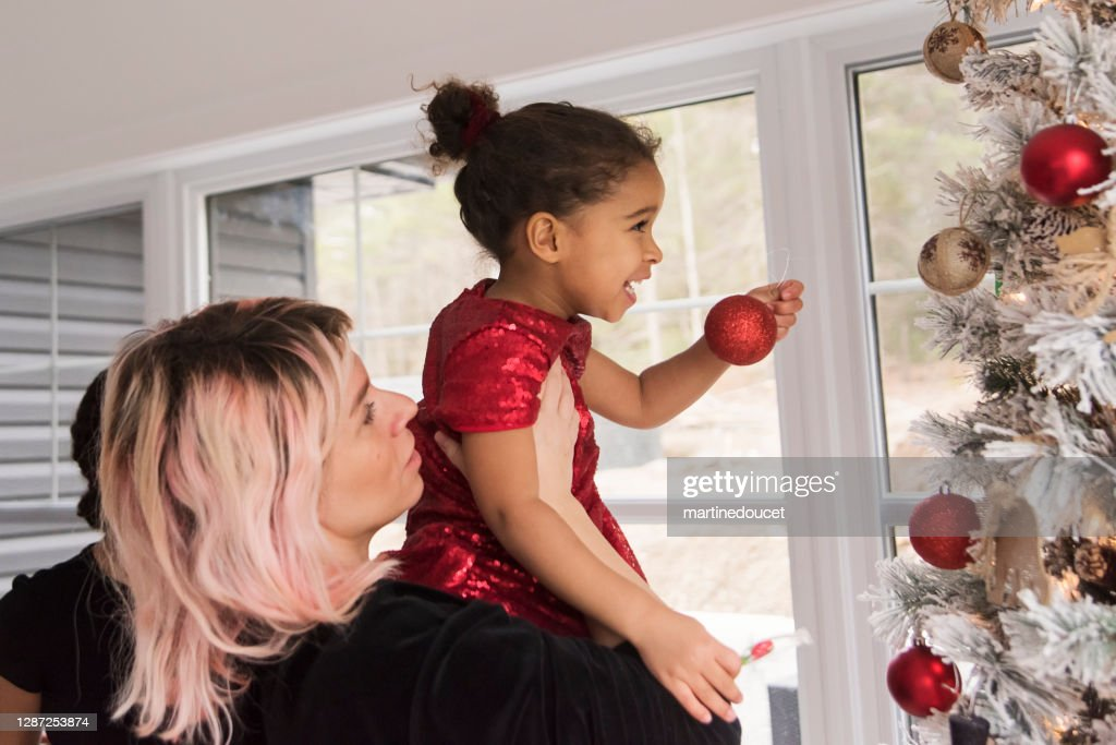 Mixed-race mother and daughter decorating the Christmas tree. : Stock Photo