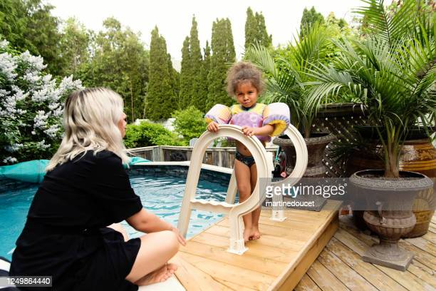 """mixed-race mother and toddler daughter having fun in the pool. - """"martine doucet"""" or martinedoucet stock pictures, royalty-free photos & images"""