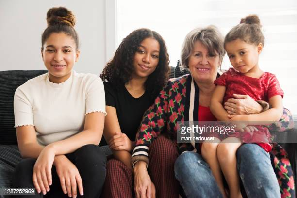 """mixed-race portrait of grandmother and granddaughters in living room. - """"martine doucet"""" or martinedoucet stock pictures, royalty-free photos & images"""