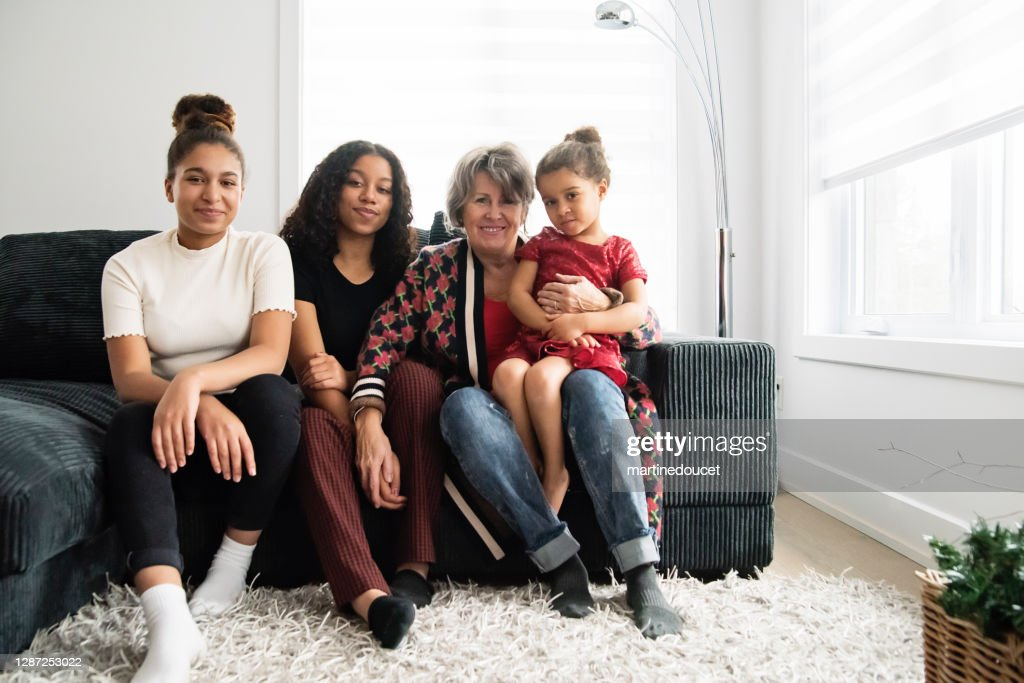 Mixed-race portrait of grandmother and granddaughters in living room. : Stock Photo