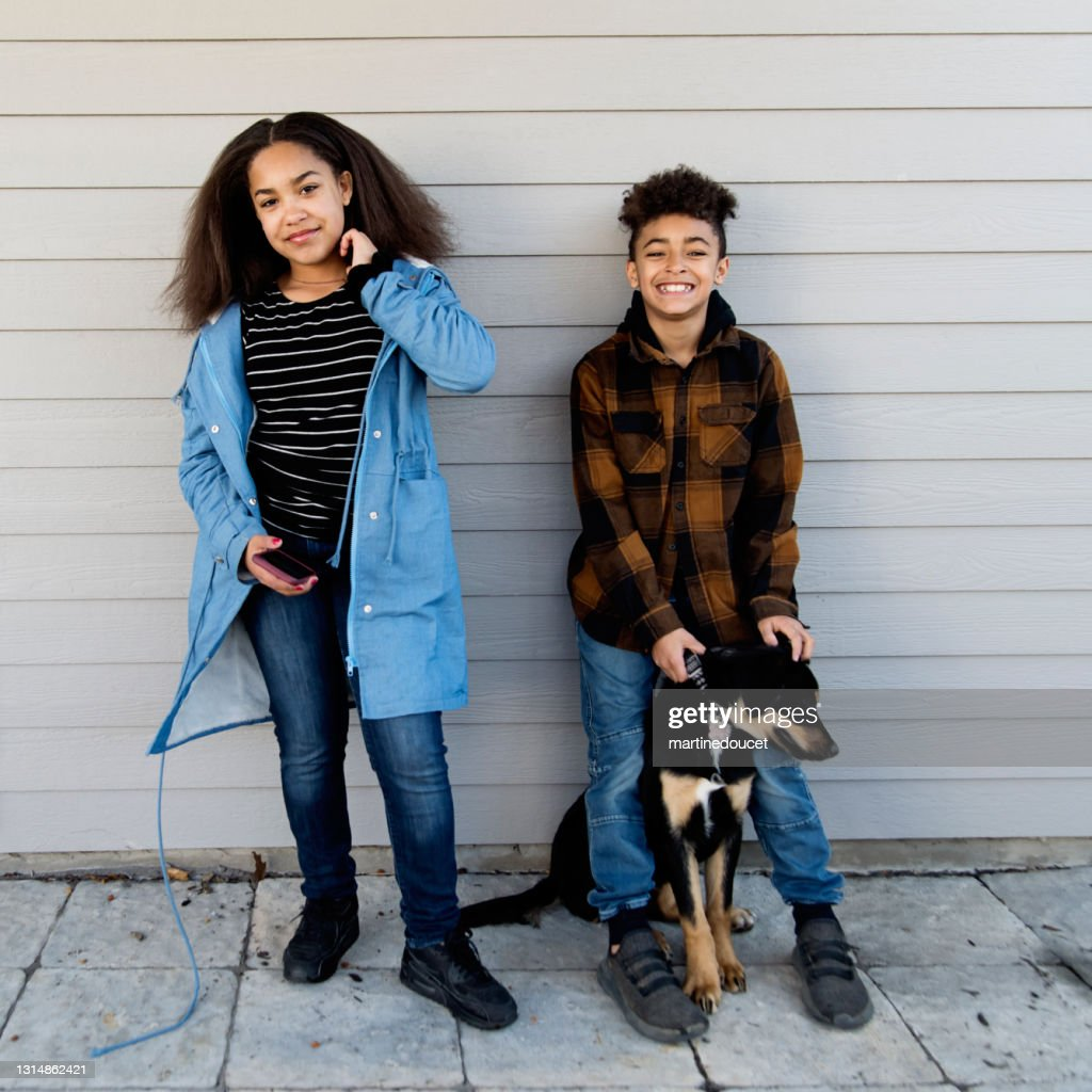 Mixed-race preteen siblings portrait with dog outdoors. : Stock Photo