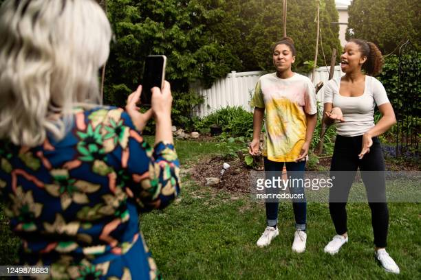 """mixed-race sisters being filmed by mother in backyard. - """"martine doucet"""" or martinedoucet stock pictures, royalty-free photos & images"""