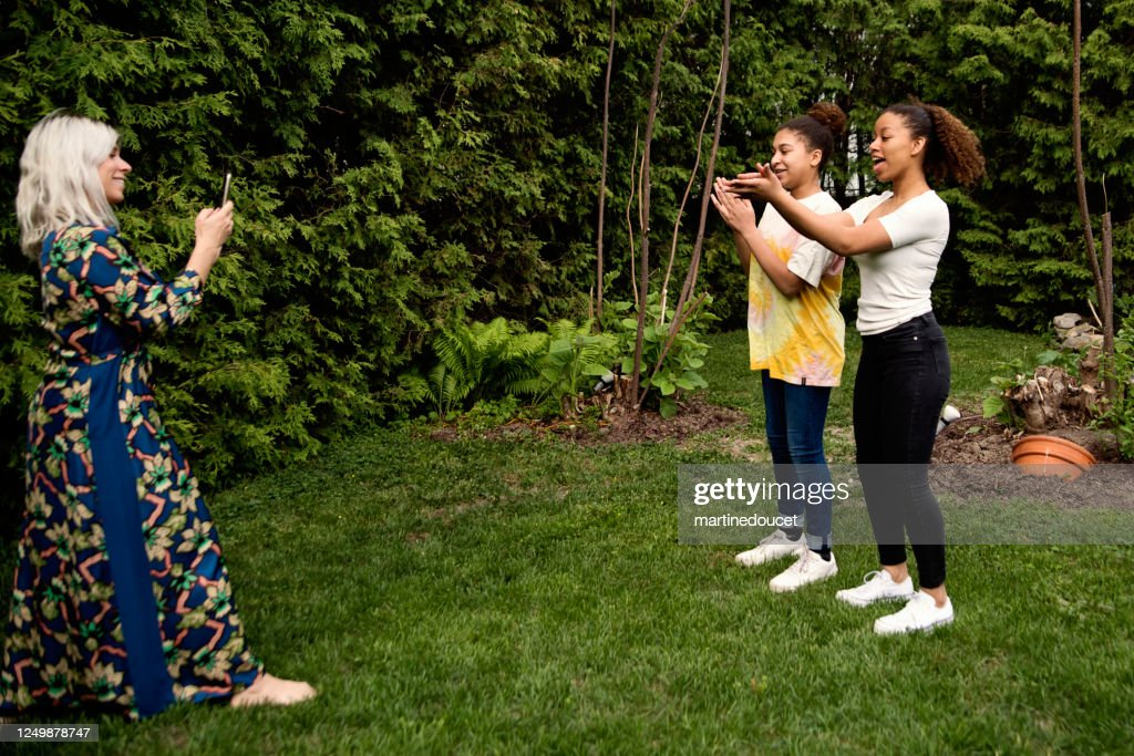 Mixed-race sisters being filmed by mother in backyard. : Stock Photo