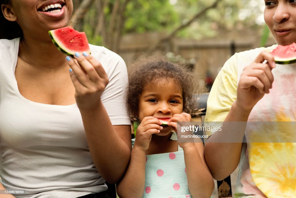 Mixed-race sisters eating watermelon in backyard. : Stock Photo