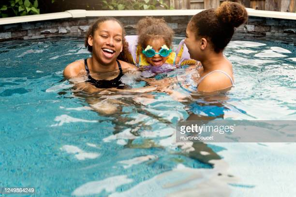 """mixed-race sisters having fun in the backyard pool. - """"martine doucet"""" or martinedoucet stock pictures, royalty-free photos & images"""