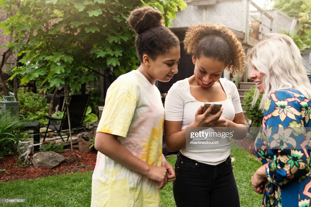 Mixed-race sisters looking at mobile phone with mother in backyard. : Stock Photo