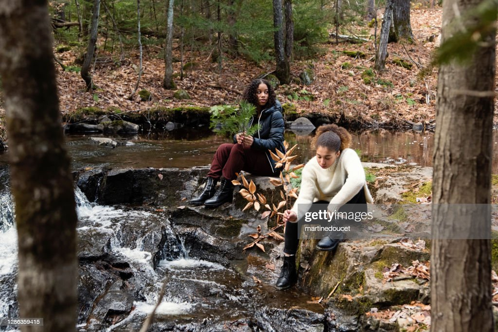 Mixed-race sisters relaxing on river side in autumn nature. : Stock Photo