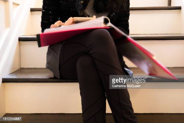 mixed-race teen female student reading while sitting on steps & holding smart phone - college admission stock pictures, royalty-free photos & images