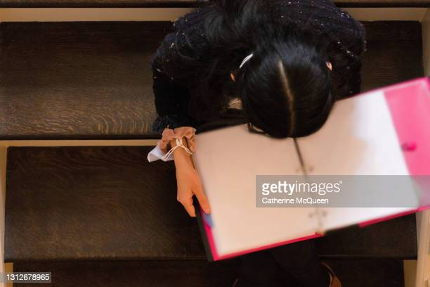 mixed-race teen female student reading while sitting on steps - college admission stock pictures, royalty-free photos & images