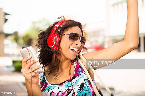 Mixed-Rennen teen Mädchen hört Musik.  Kopfhörer, Smartphone in der Innenstadt.