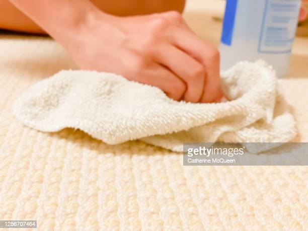 mixed-race teen girl tries to remove stain from carpet - carpet stock pictures, royalty-free photos & images