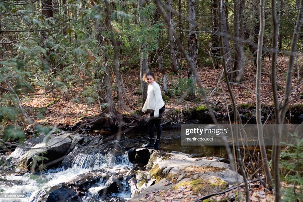 Mixed-race teenage girl on river side in autumn nature. : Stock Photo