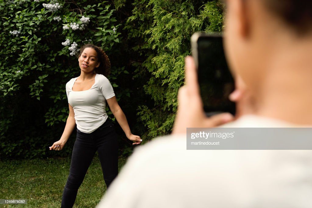 Mixed-race teenage sisters filming with mobile phone in backyard. : Stock Photo