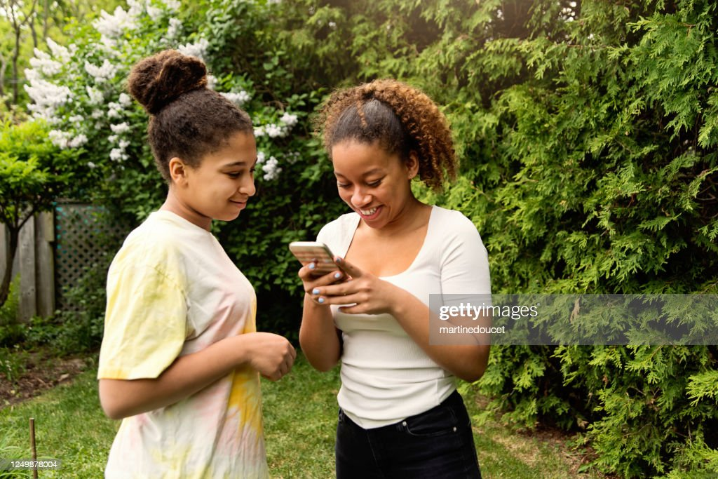 Mixed-race teenage sisters looking at mobile phone in backyard. : Stock Photo