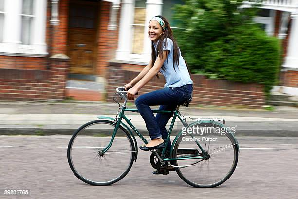 Mixed-race teenager riding bicycle