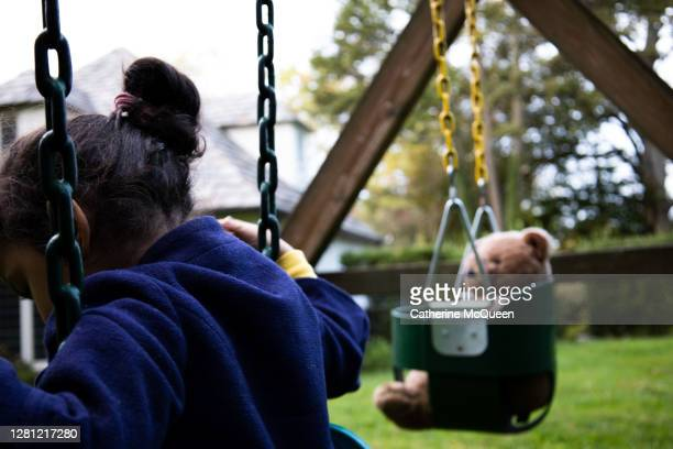 mixed-race toddler girl enjoys a socially-distanced playdate with her stuffed teddy bear - good; times bad times stock pictures, royalty-free photos & images