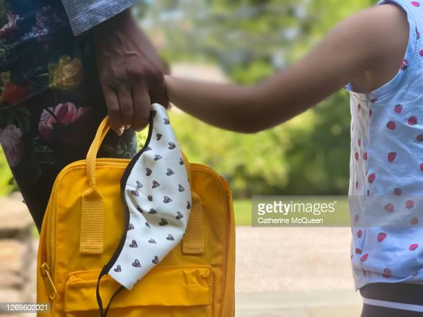 mixed-race toddler & her african-american mother await school bus for first day of preschool while holding hands - education stock pictures, royalty-free photos & images