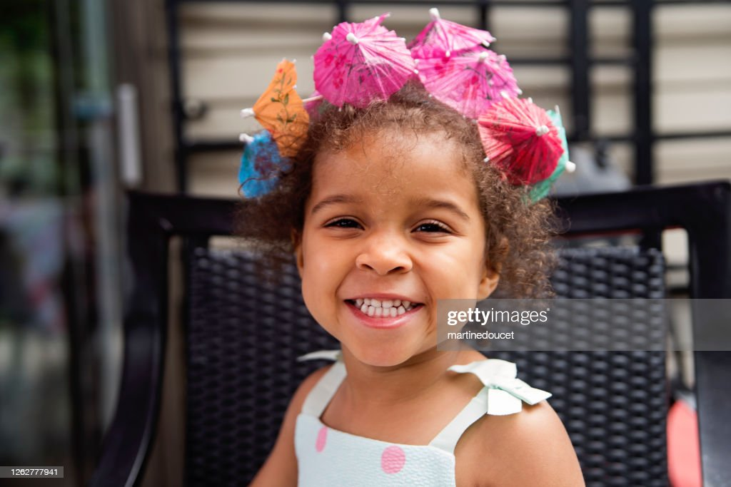 Mixed-race toddler playing at table outdoors in summer. : Stock Photo
