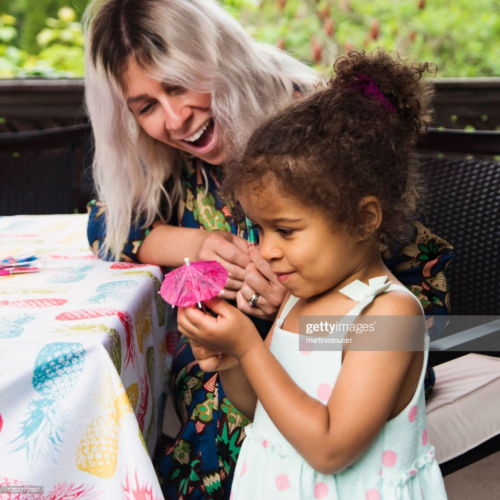 Mixed-race toddler playing at table outdoors with mother. : Stock Photo