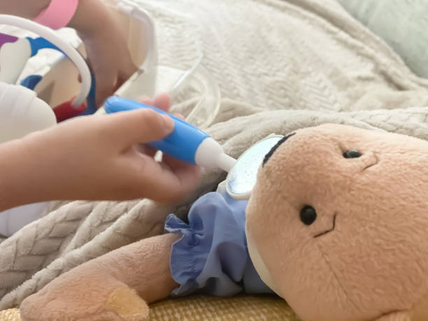 mixed-race toddler plays doctor with teddy bear and toy medical kit