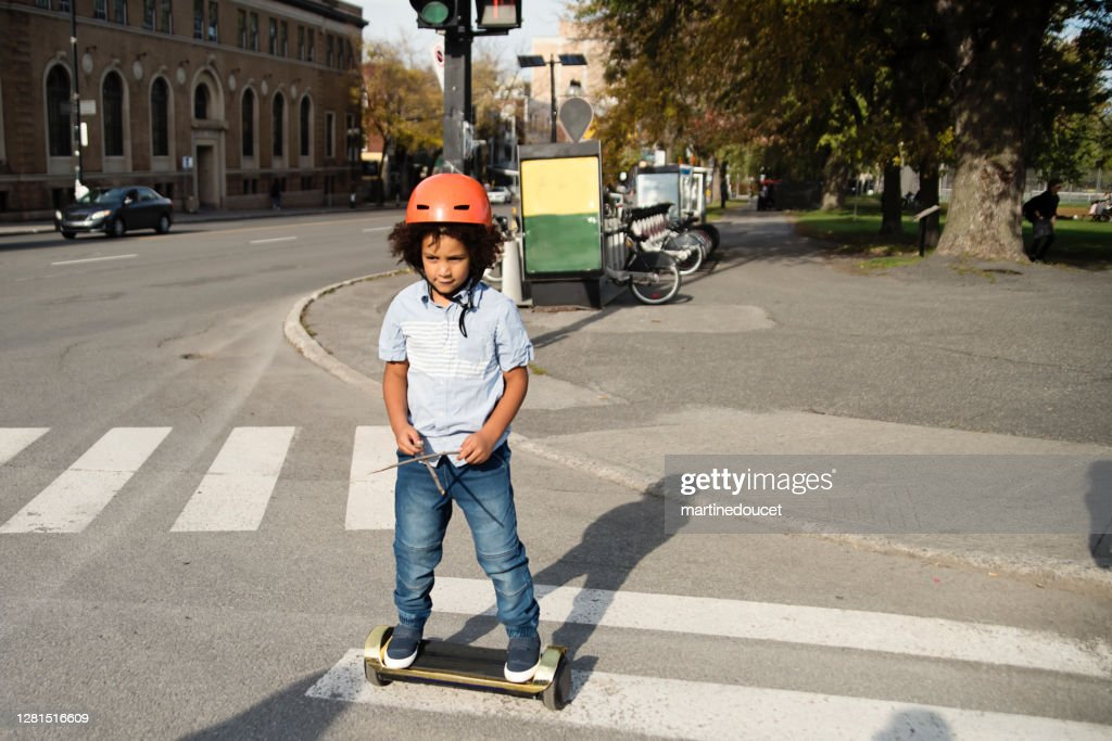 Mixed-race young boy on electric skateboard crossing street. : Stock Photo