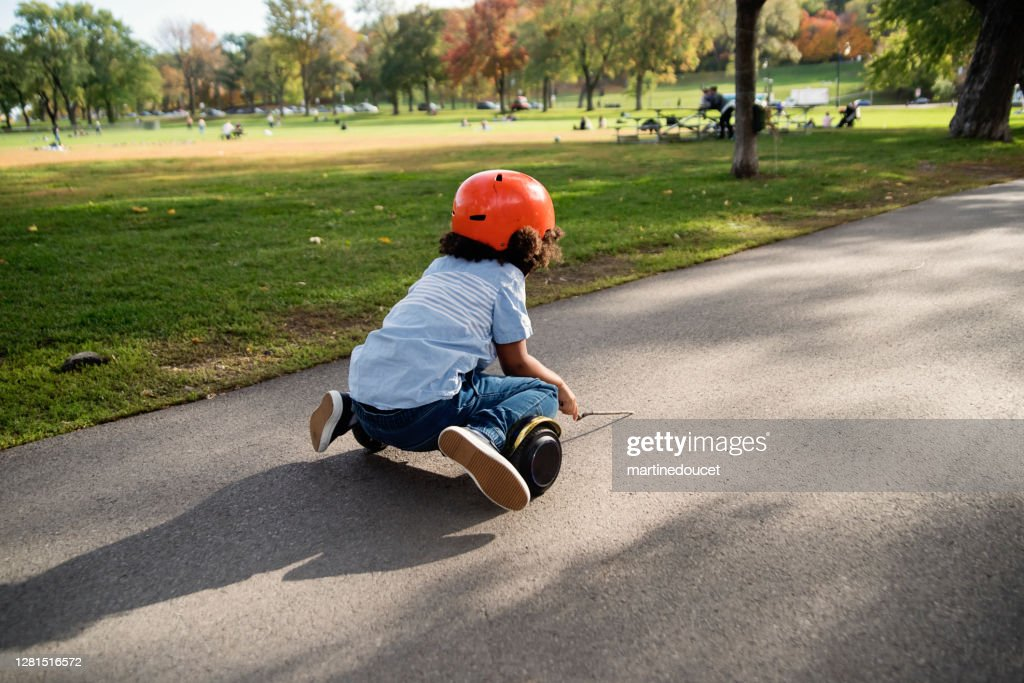 Mixed-race young boy on electric skateboard in urban park. : Stock Photo