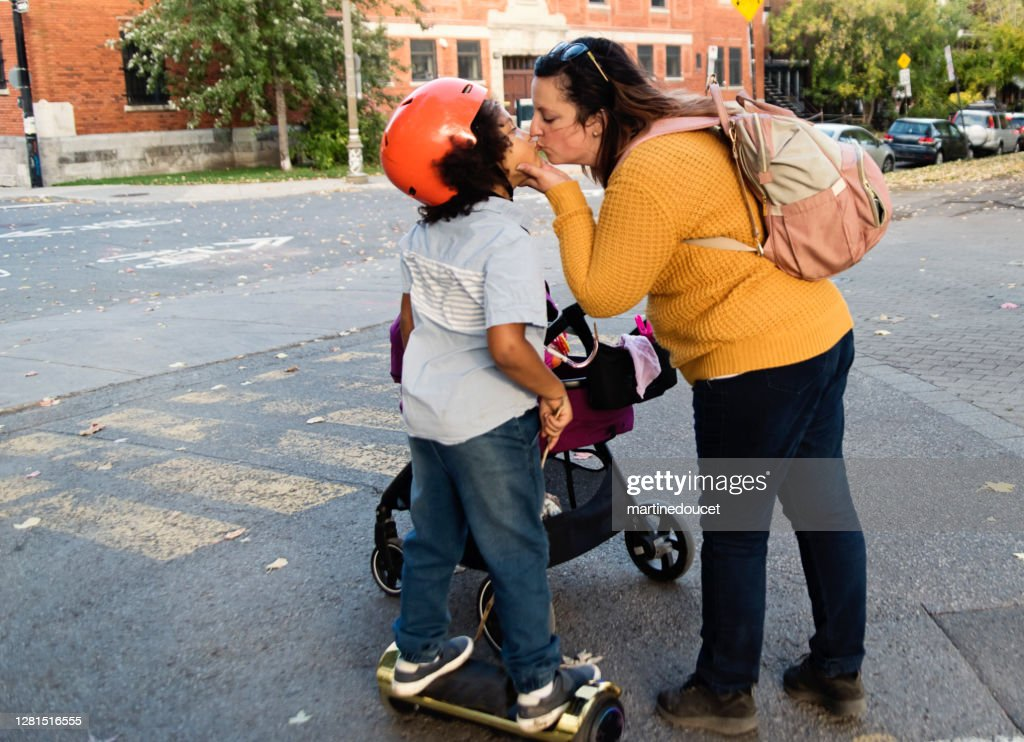 Mixed-race young boy on electric skateboard kissing mother. : Stock Photo