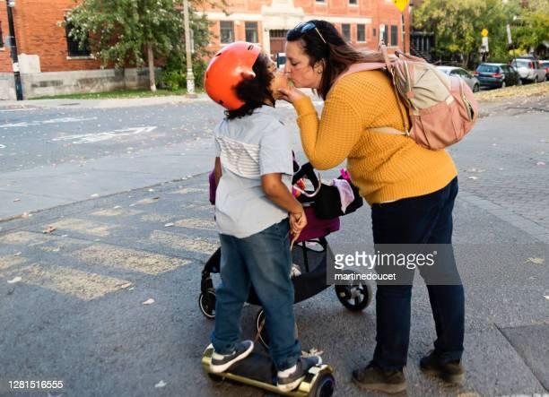 "joven de carrera mixta en patineta eléctrica besando a la madre. - ""martine doucet"" or martinedoucet fotografías e imágenes de stock"