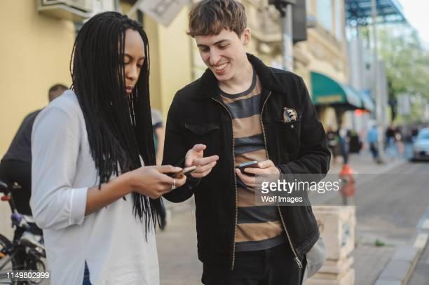 mixed-race young couple using mobile phone - mensagem com foto imagens e fotografias de stock