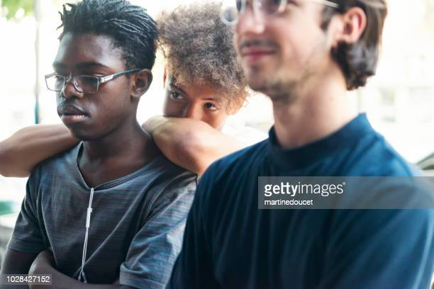 Mixed-race young men waiting in line outdoors.