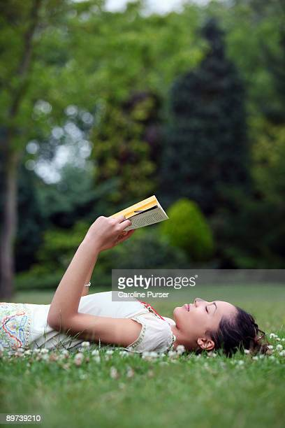 Mixed-race young woman lying on grass and reading