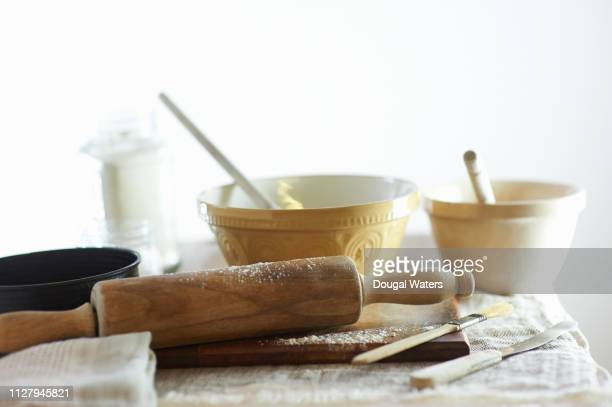 mixing bowls and cake making utensils on table at home. - cooking utensil stock pictures, royalty-free photos & images