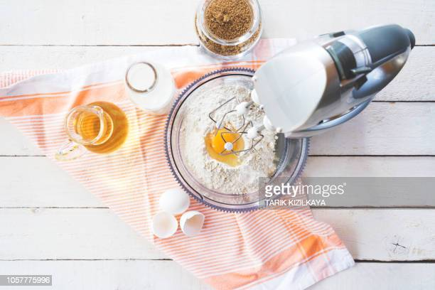 mixing flour and eggs with a table mixer - electric mixer stock pictures, royalty-free photos & images