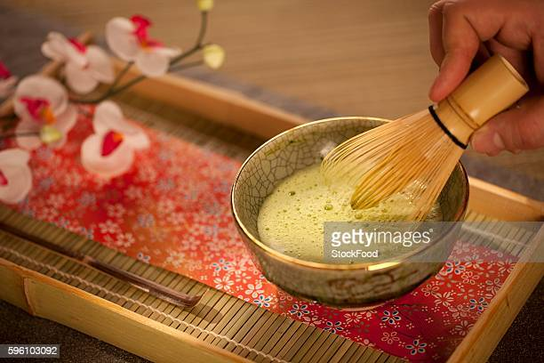 Mixing Japanese Matcha Green Tea in a Ceremonial Bowl with Whisk