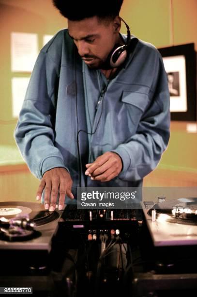 DJ mixing music at record player in nightclub