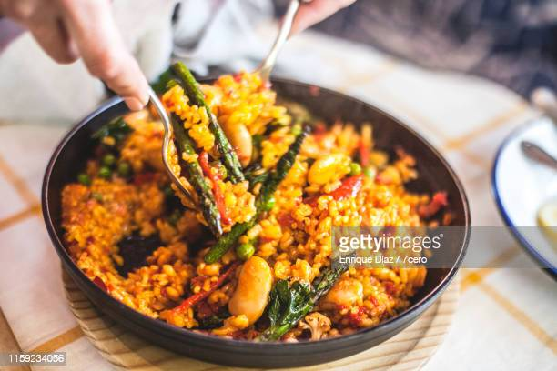 mixing up the vegetable paella - spanish culture stock pictures, royalty-free photos & images