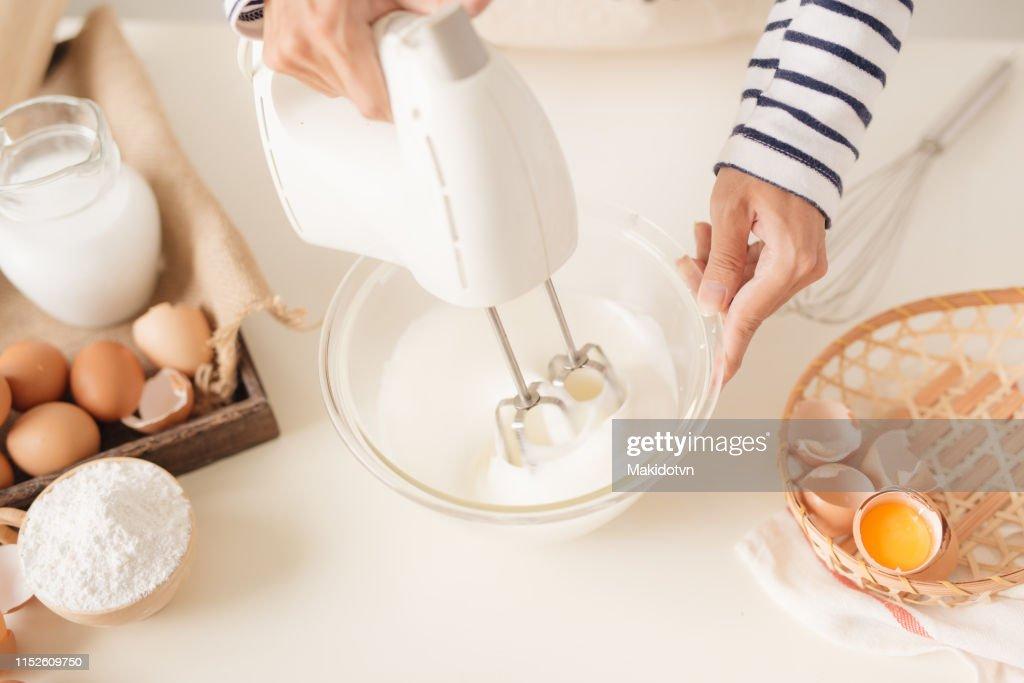 Weißei-Ei-Creme in Schüssel mit Motormixer mischen, Kuchen backen : Stock-Foto